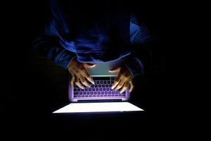 Hooded hacker Man with laptop stealing personal data from internet