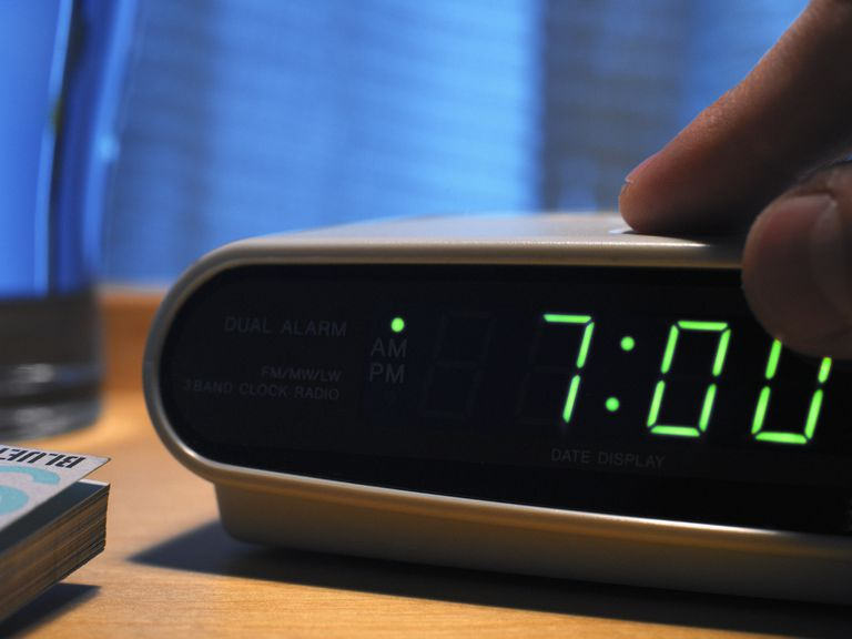 A person pressing a button on a digital alarm clock.