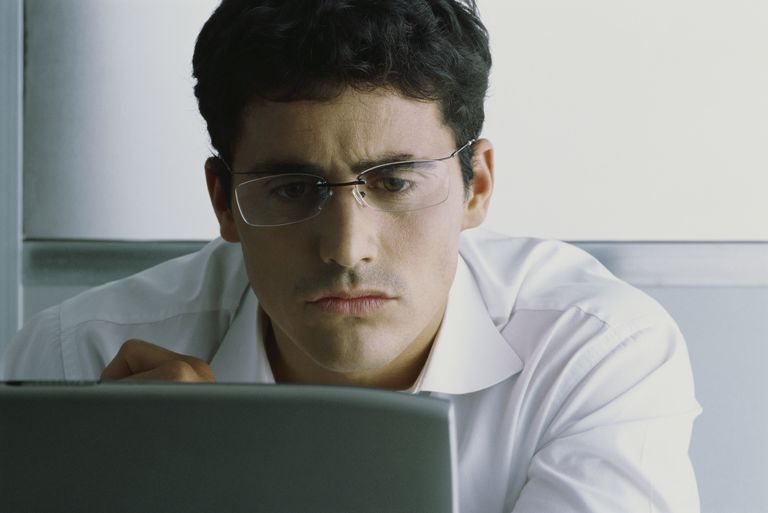 Man in glasses using laptop computer