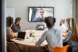 An office conference room with a video conference call on a screen on the wall