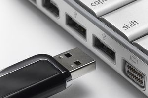 USB flash drive about to connect to laptop, close-up.