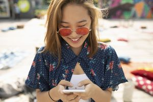 Fashionable girl texting on smartphone