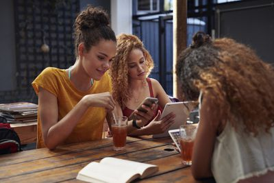 Three young women using smart devices