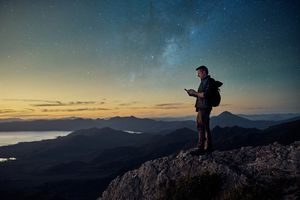 Man stands on a mountain looking at his phone under the stars