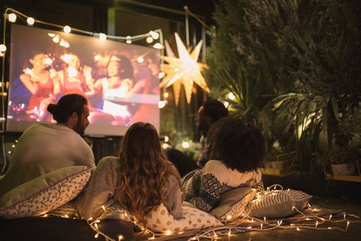Several people leaning back on cushions, watching a projector screen surrounded by lights.