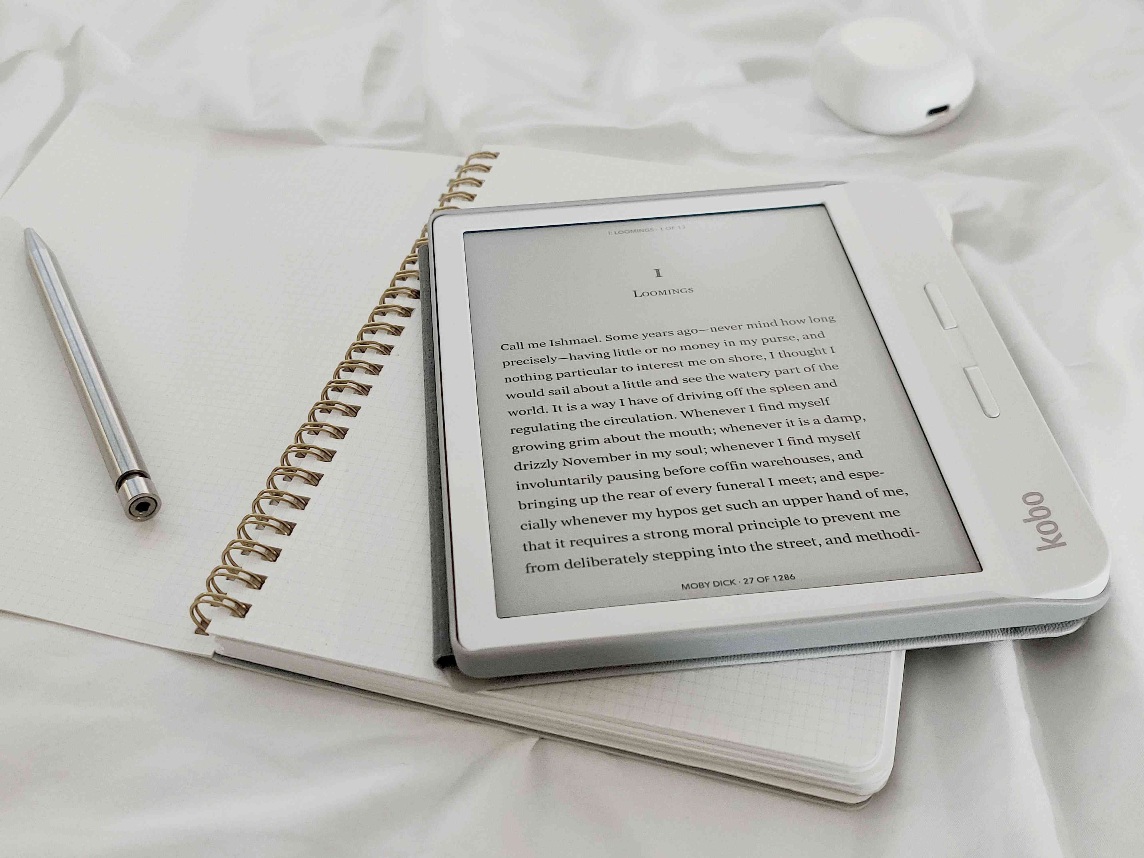 A white Kobo e-reader sitting on top of a notebook.