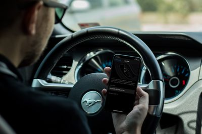 A man holding an iPhone in his car.