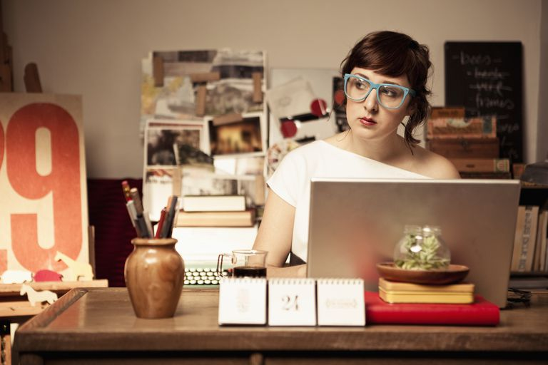 Woman working in home office writing an online diary or blog