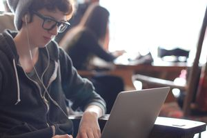 Teenager on laptop in public space wearing earbuds