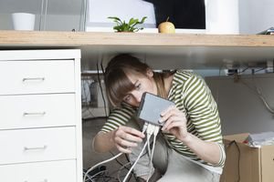 A woman crouching under a desk looking at a router