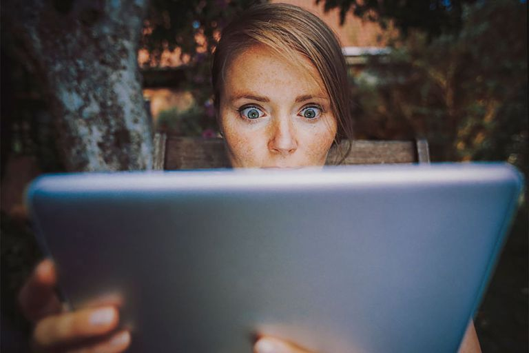 Woman looking at iPad with surprised eyes