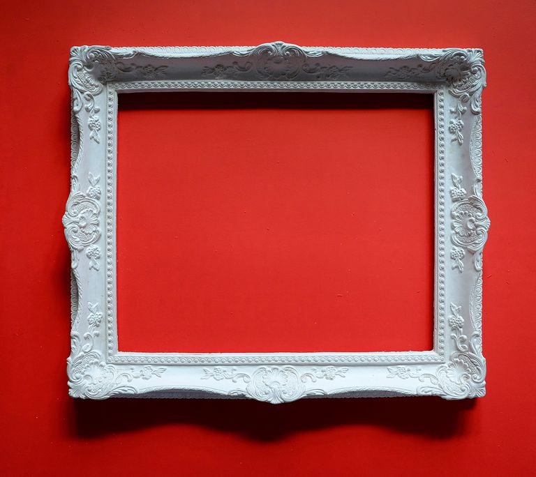 Empty white picture frame hanging on red wall