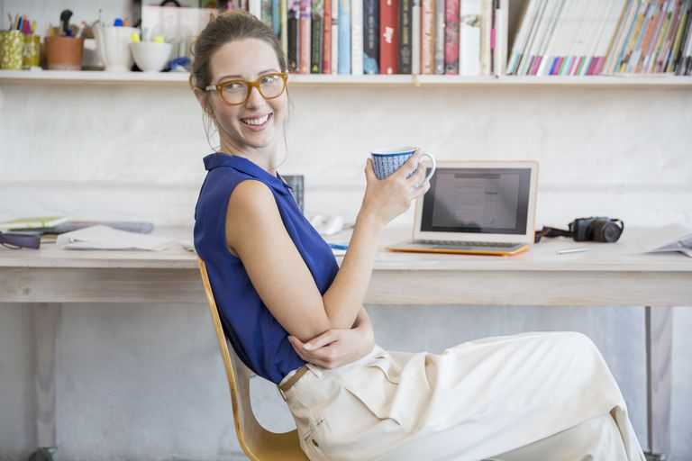 Young woman sitting with mug in home office