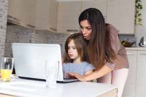 Cute girl and mother using laptop at home