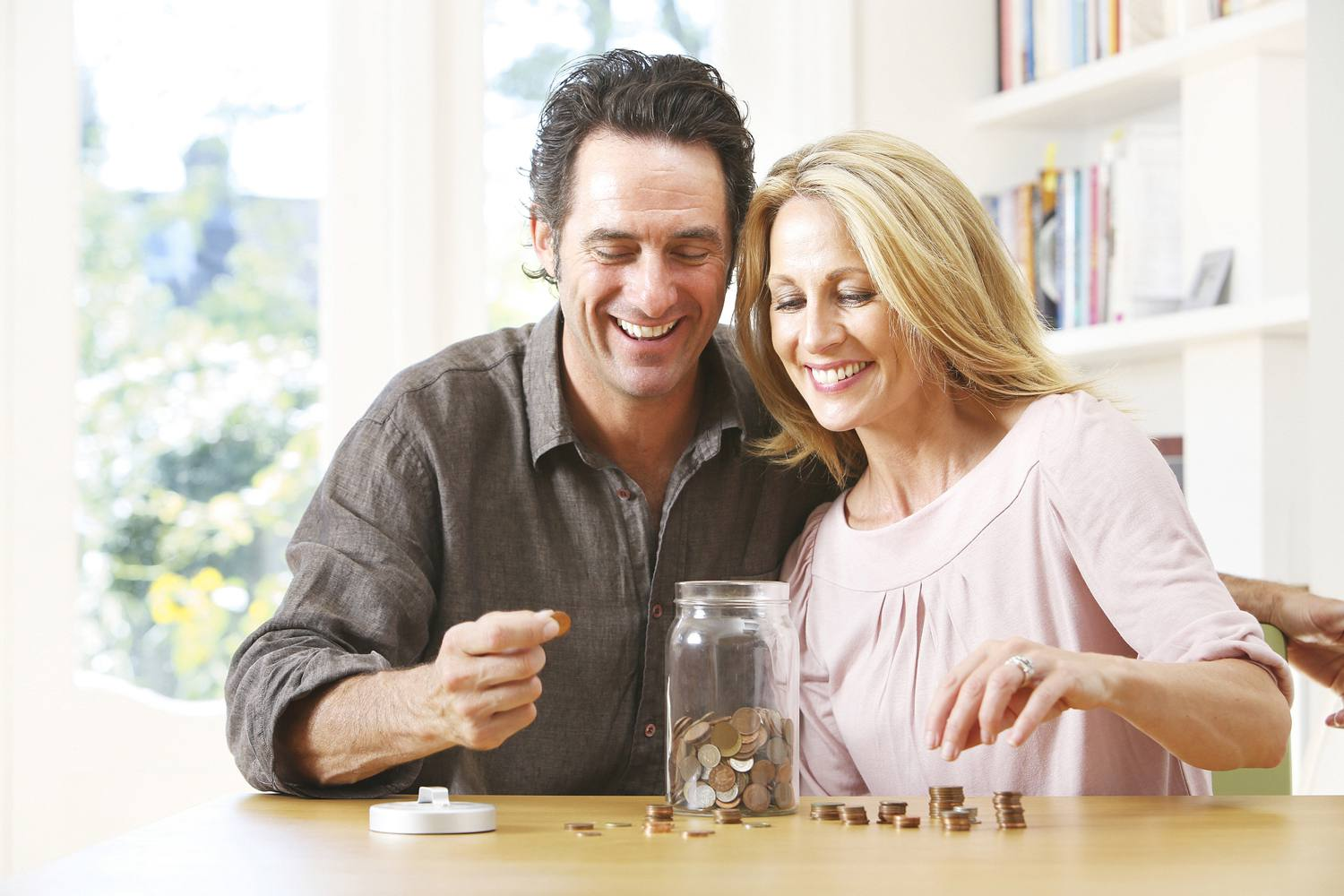 Couple sorting money out of a jar of change