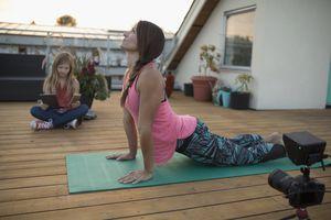 vlogging upward facing dog yoga pose on patio deck