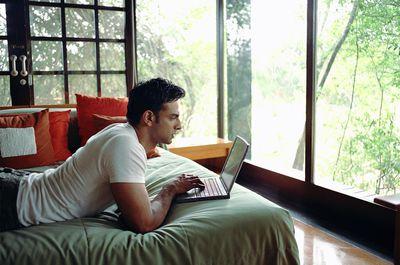 Gamer on bed using laptop