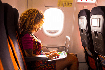 Image of a woman using a laptop on a plane.