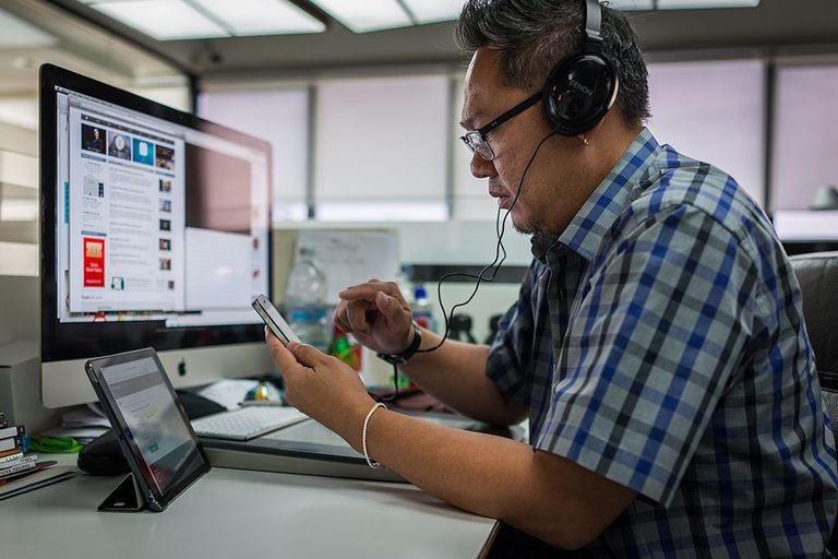 man in office using iMac and iPhone