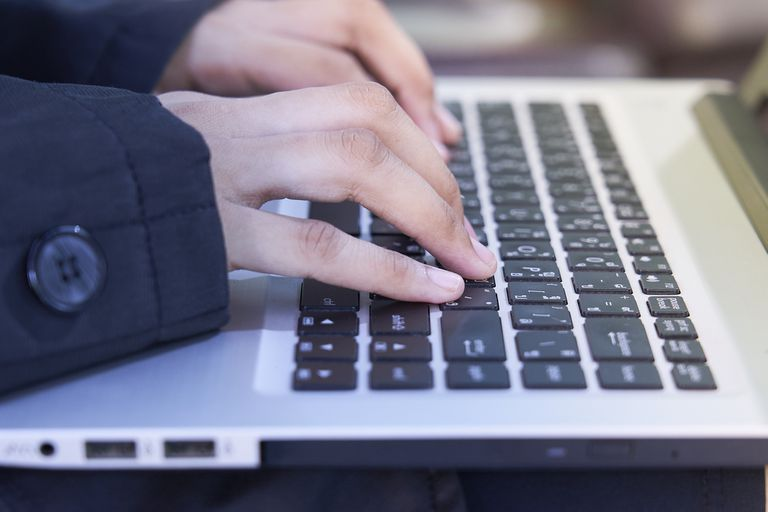 Woman's hands using keyboard on laptop