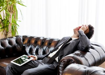 Man on couch frustrated with his tablet