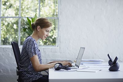A side view of a woman sitting at her desk typing at a laptop