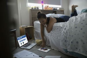 A student lays on her bed and uses a tablet while her laptop is open to the Best Buy Student Discounts page