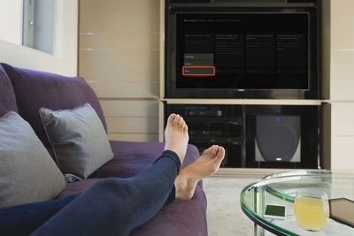 A person on the couch with the TV being set to appear offline on Xbox One