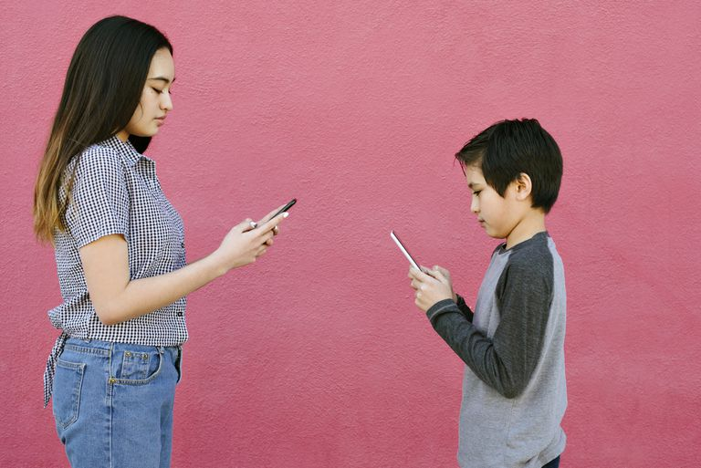 Teenager and young boy on phones facing each other