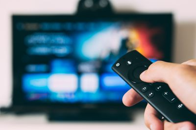 Someone holding a Fire TV remote with a TV blurred out in the background.