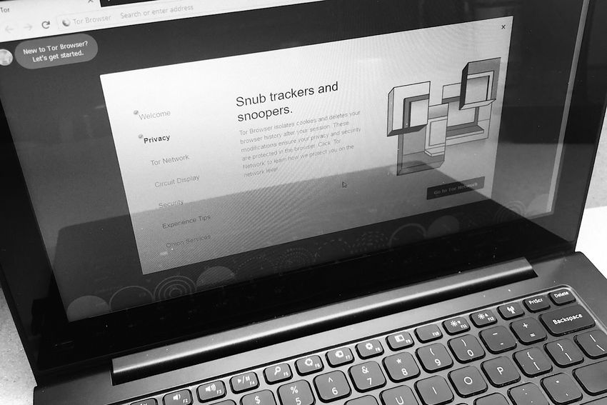 "Black and White photo of a laptop with the TOR Browser open to an explanatory Privacy screen that says ""Snub trackers and snoopers."""