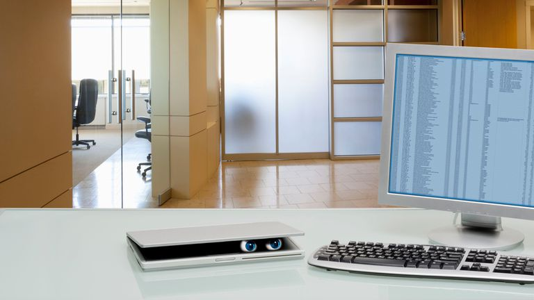 Eyes peering out of laptop on office desk