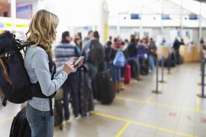 Tourist texting at airport check-in desk