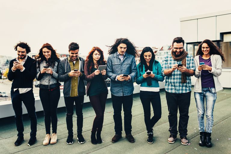 A group of people standing on a roof, all looking at their phones