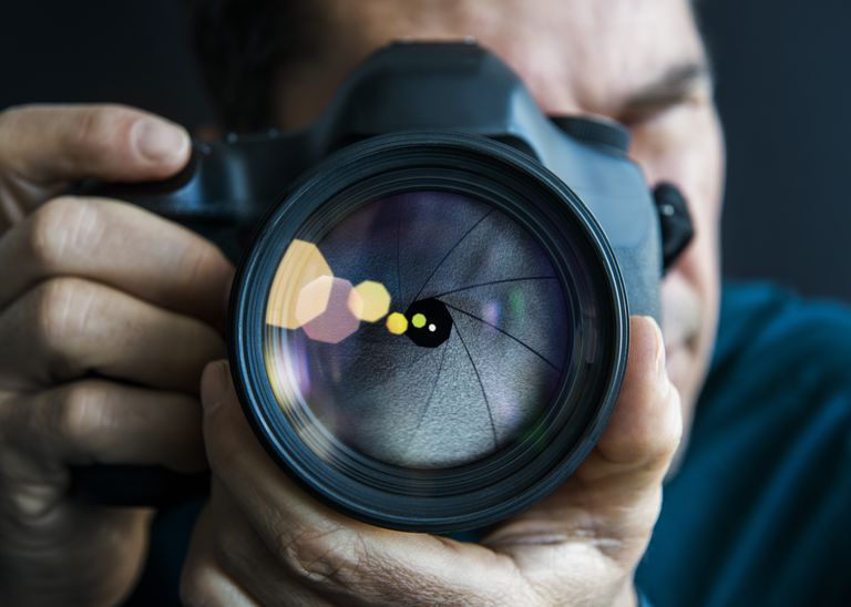 Man holding camer, close-up of lens