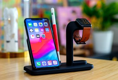 An Apple iPhone, Apple Watch, and Apple Pencil on a charging stand.