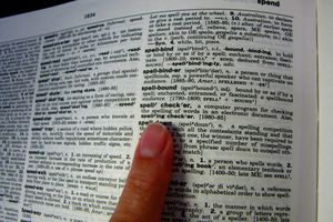 Finger pointing to Spell Check in a dictionary