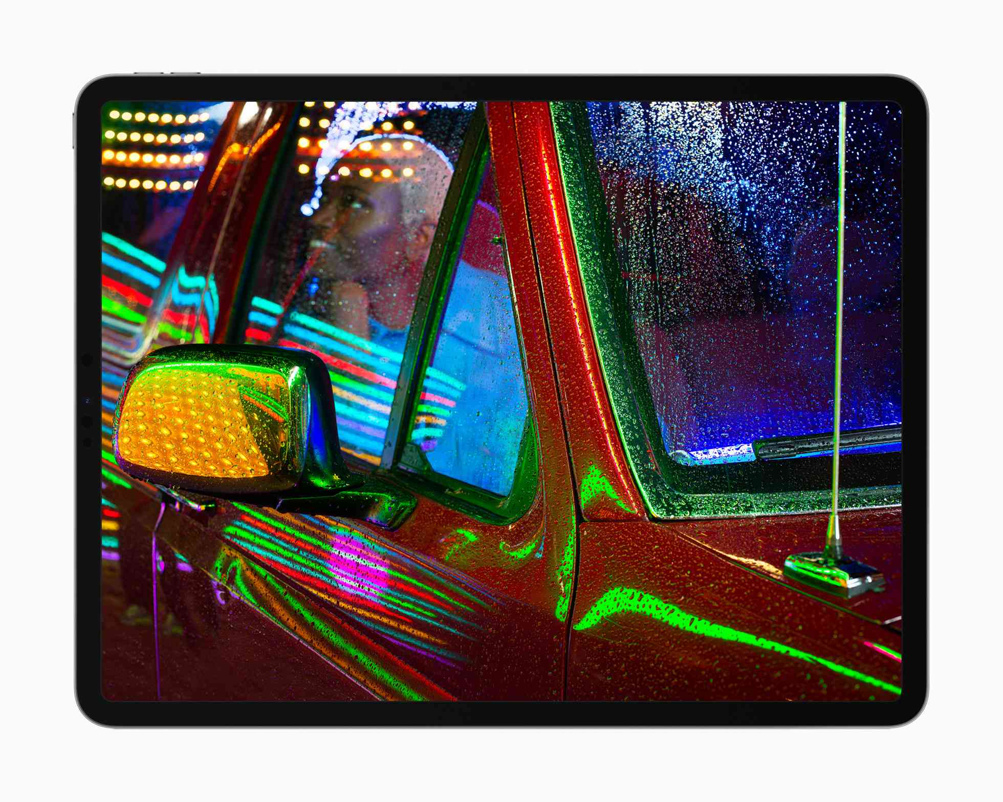 Apple iPad Pro liquidXDR display showing a photo of someone inside a pickup truck with neon lights reflecting off the metal and glass.
