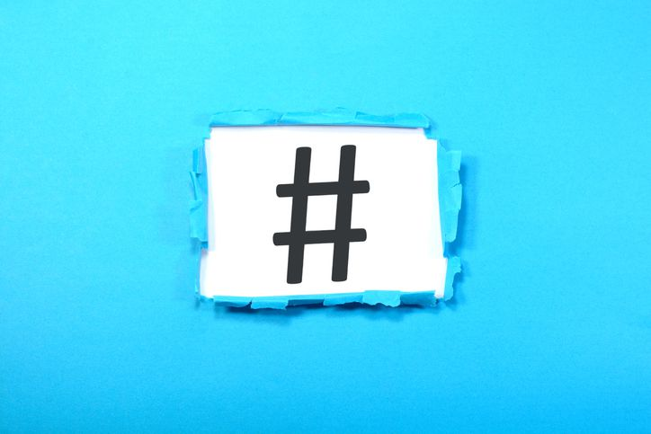 HashTag sign shown on a blue ripped paper.