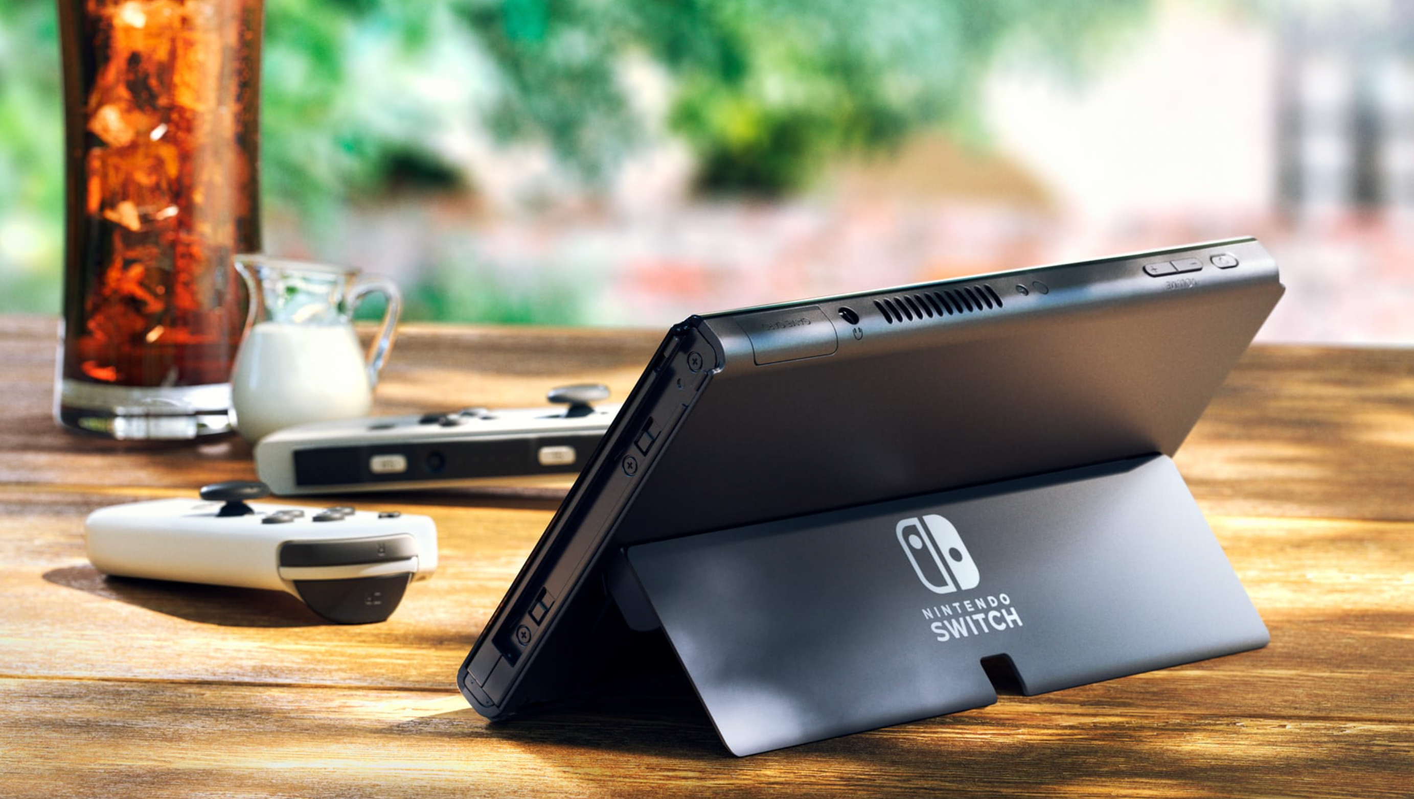 Nintendo Switch OLED Model standing using its kickstand next to white joy-con controllers