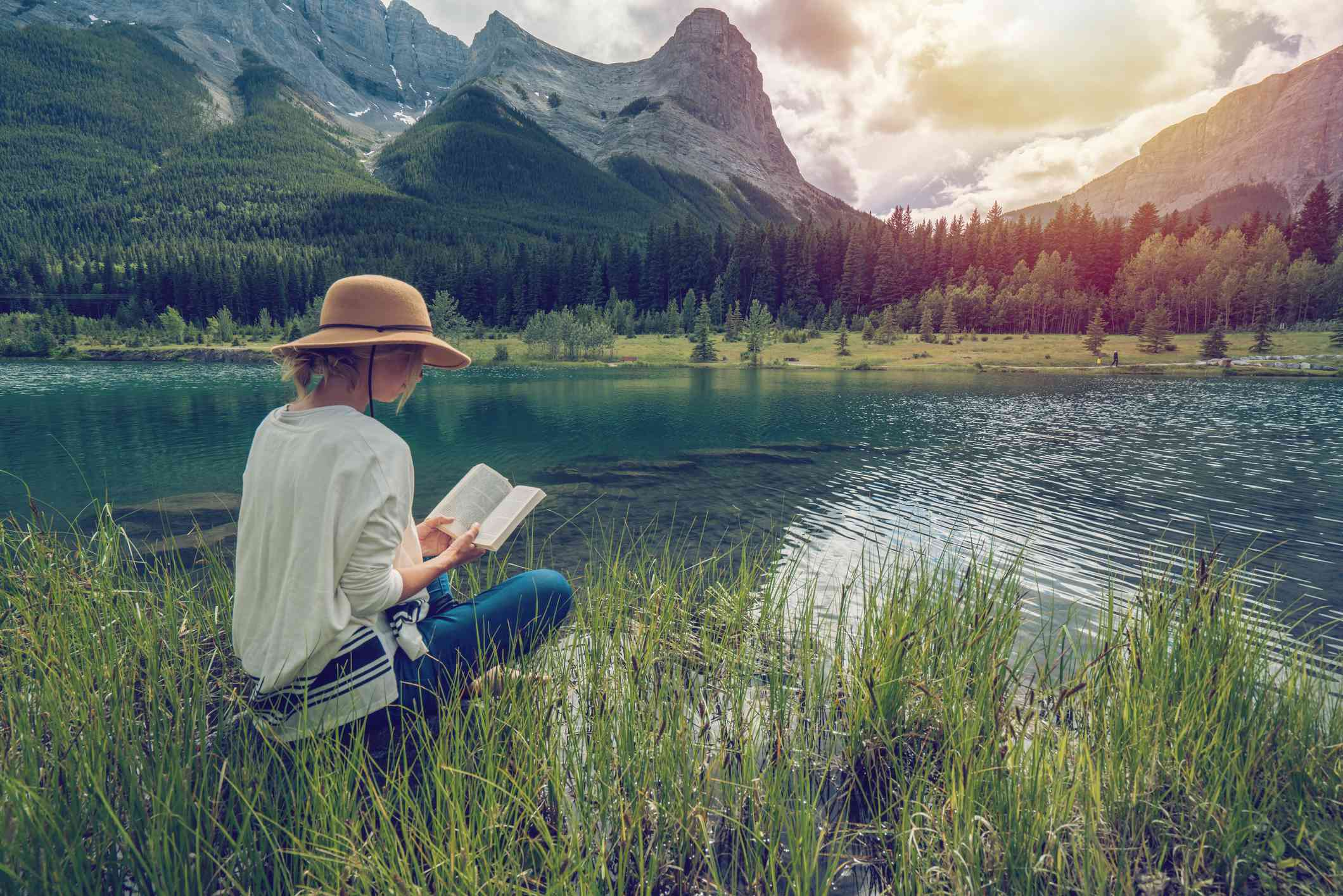 A woman reading a paperback by the lake with mountains in the background.