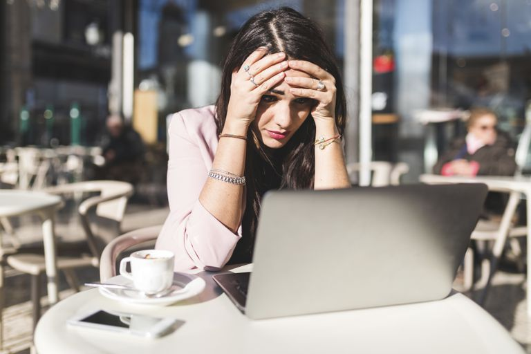 A woman is looking frustrated as she sits at a cafe with her laptop computer open.