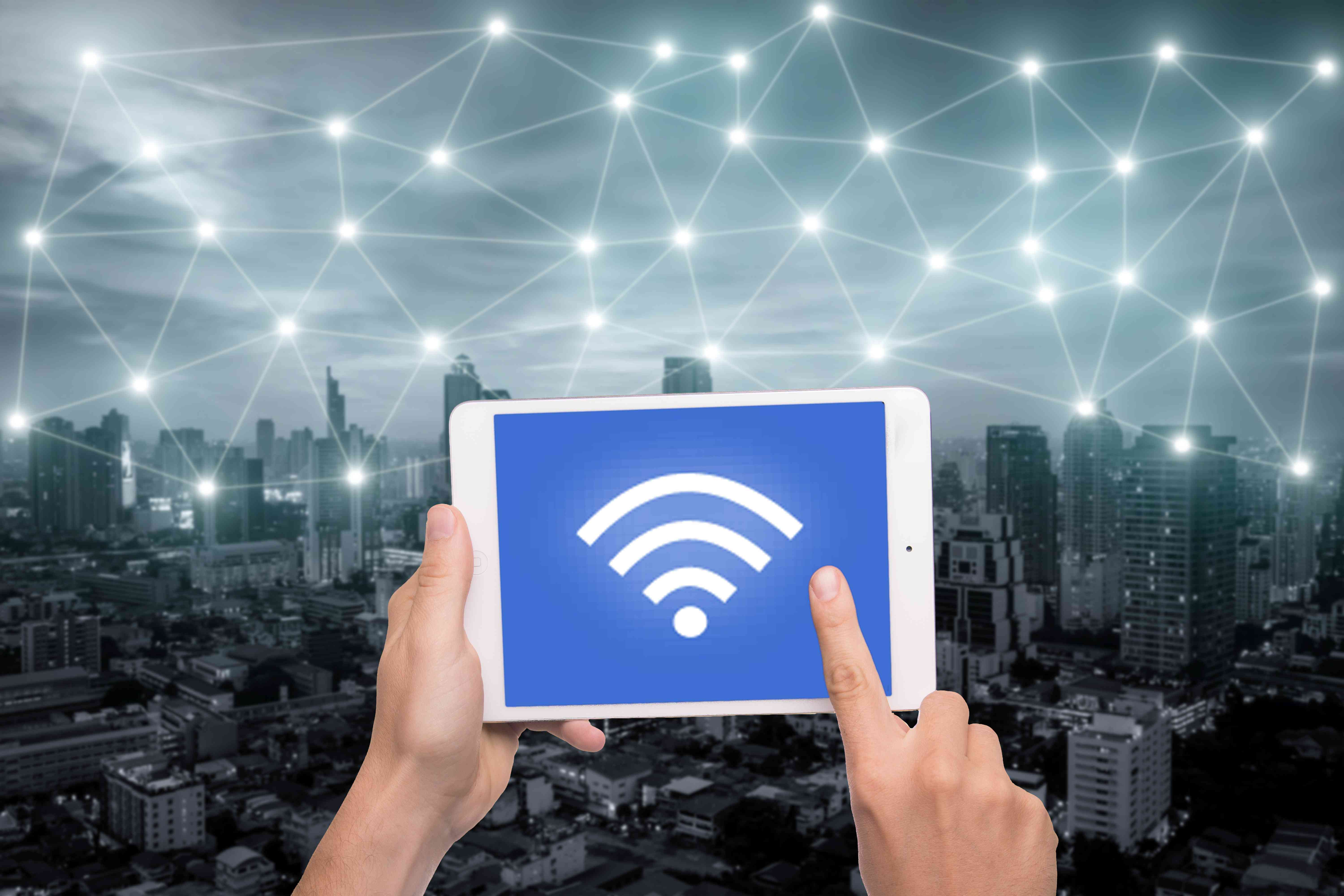 Hand holding tablet with wifi icon on city and network connection concept. Bangkok smart city and wireless communication network, abstract image visual, internet of things.