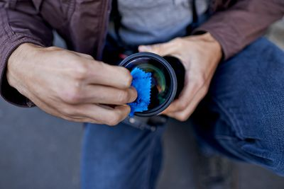 A young man removing the lens from his camera
