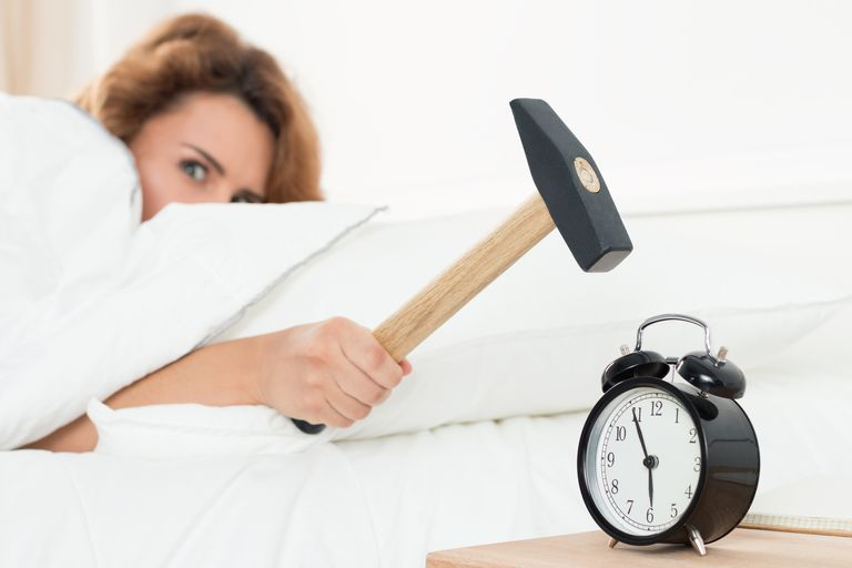 Woman hitting alarm clock with hammer