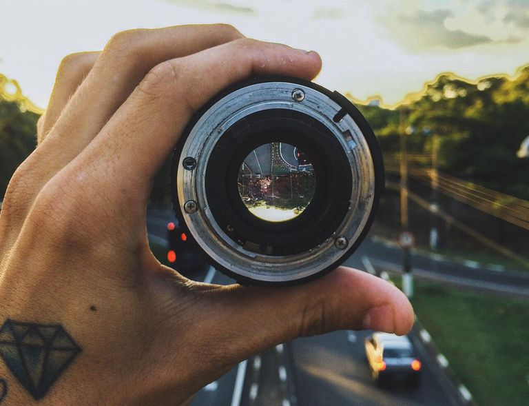 Hand holding camera lens with sunset and road in background