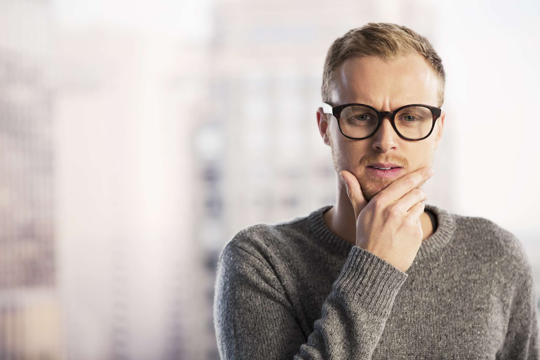 Man in glasses rubbing chin