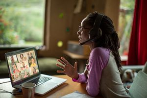 A woman sitting at a desk with a headset on looking at a laptop with a video conference call playing out