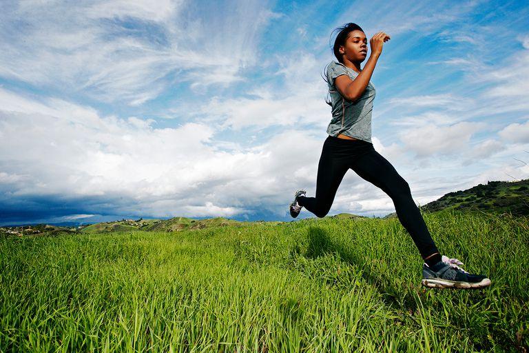 Black athlete running in rural field