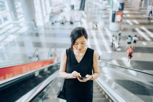 A woman is on an escalator in a shopping mall looking at her phone.